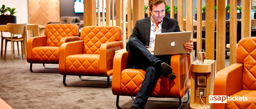 Man with an Apple computer work before flight in Airport's Business lounge - ASAPtickets