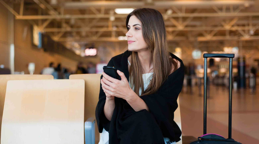 A smiling woman waits at the airport holding her mobile cell phone - Book Last-Minute Flights