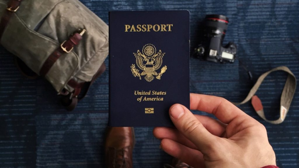 A man holds a United States passport with travel items in the background - Book Last-Minute Flights