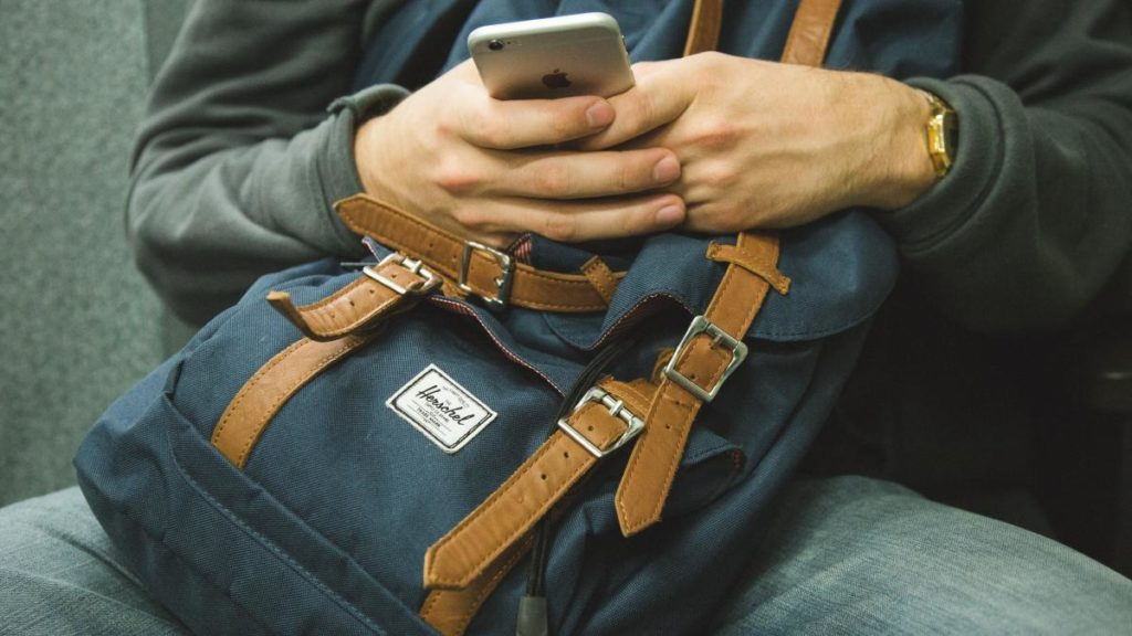 Man holding iPhone and Herschel Backpack | Free Airport WiFi Passwords
