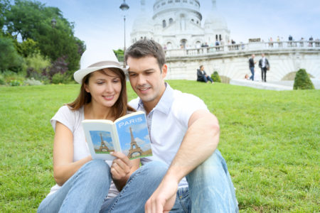5 Best Travel Guidebooks Europe | Couple in Paris sitting in front of Sacre Coeur Basilica