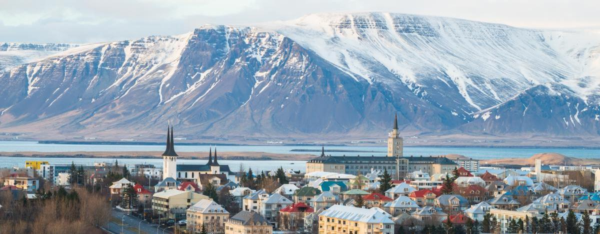 The city Reykjavik in Iceland with the mountain Mount Esja in the background on a stopover with Icelandair when flying to Europe - How to find the cheapest flights to Europe