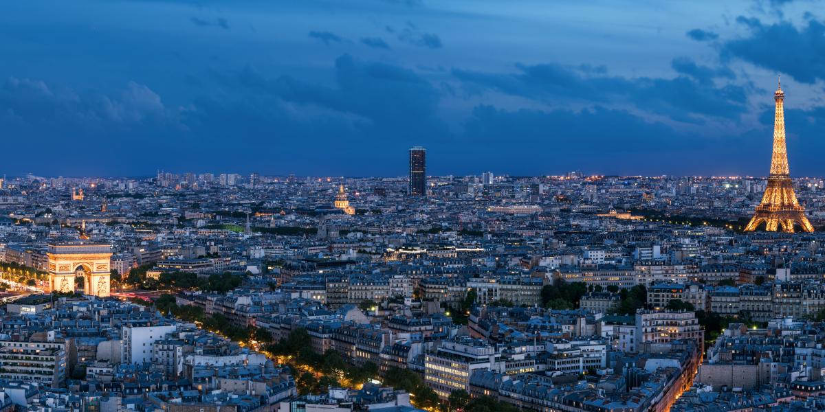 Nighttime view of Paris, France with the Eiffel Tower, Arc de Triomphe, and Sacre Coeur- How to Find the Cheapest Flights to Europe
